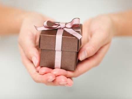 gift giving: Present   gift  Close up of hands holding small gift with ribbon  Stock Photo