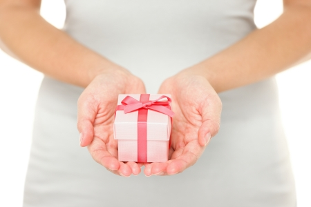giving: Hands holding gift   present in isolated on white background  Closeup of Female hands giving the gift