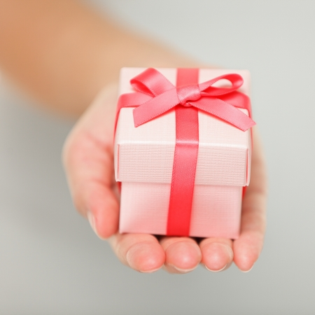 Gift closeup  Red present of gift in closeup in woman hand  photo