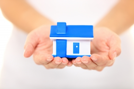sell house: Home - new house concept  Woman holding model house Stock Photo