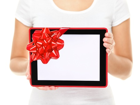Tablet computer screen gift  Closeup of touch pad tablet computer screen with red gift ribbon  Christmas gift or present isolated on white background  Stock Photo - 16480554