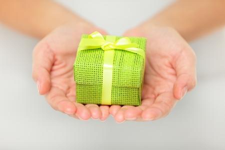 dar un regalo: Peque�o regalo decorativo colorido verde celebrada en extendidas las manos ahuecadas como un regalo sorpresa de Navidad para un ser querido
