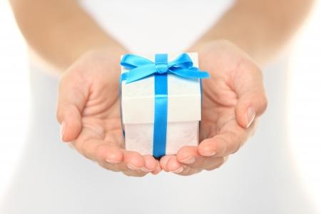 �tonnement: Coffret cadeau d�coratif attach� avec un ruban turquoise et arc soigneusement dans le creux de mains f�minines comme elle donne un cadeau surprise � un �tre cher