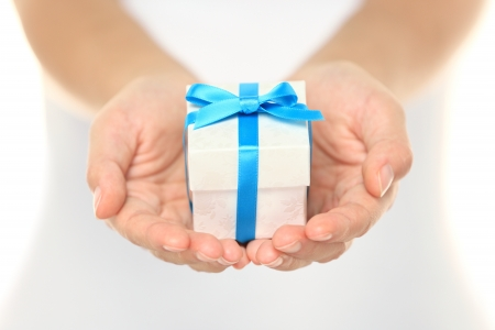 Decorative gift box tied with a turquoise ribbon and bow carefully cupped in female hands as she gives a surprise present to a loved one photo