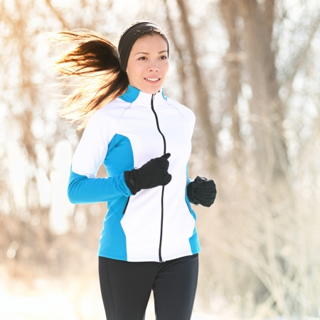 Trail running in winter. Woman fitness sport runner training outside cold winter forest path. Happy Caucasian  Asian girl in her twenties.