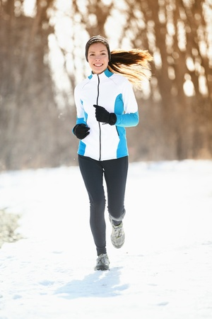 Winter running. Woman runner trail running cold winter forest landscape. Mixed race Asian / Caucasian female cross country running in warm clothes Stock Photo - 16603998