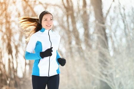 Ejecución de mujer deporte. Correr Corredor femenino en bosque de invierno frío con ropa tibia deportivo y guantes. Hermosa modelo de ajuste femenino asiático / caucásico gimnasio.