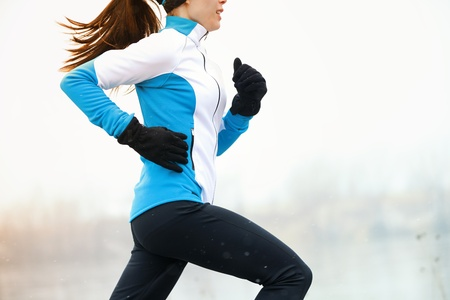 Running athlete woman sprinting during winter training outside in cold snow weather. Close up showing speed and movement. photo