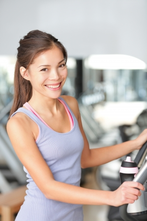 cardiovascular exercising: Fitness woman in gym training and working out on moonwalker gym equipment. Beautiful young multiracial Asian Chinese  Caucasian female model. Stock Photo