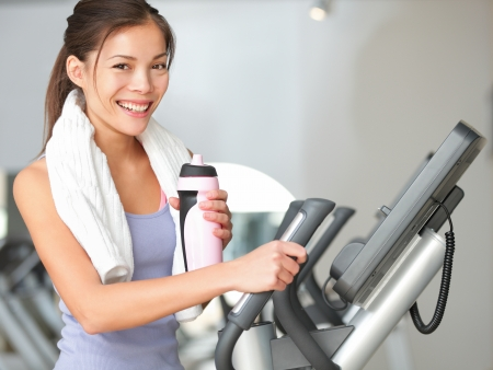 Gym woman fitness workout. Fitness girl exercising on moonwalker treadmill gym equipment. Young mixed-race Caucasian / Asian Chinese fitness model looking at camera smiling. photo