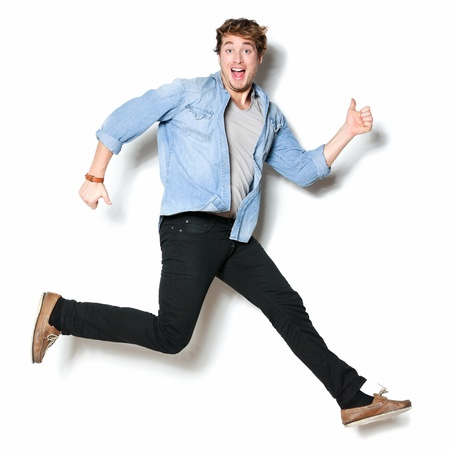 cheer full: Jumping man happy excited. Funny portrait on young casual male male model in humorous jump on white background.