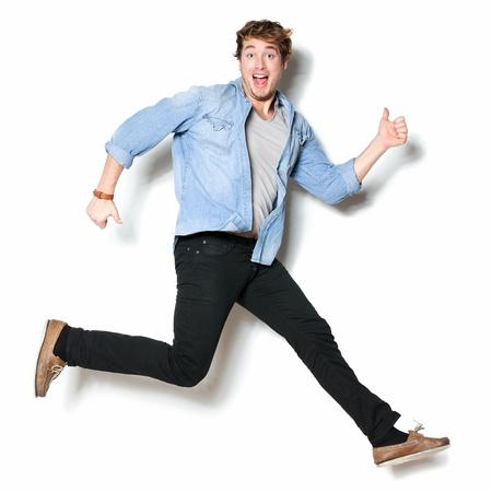 pulando: Saltando homem feliz animado. Retrato engra�ado sobre o jovem modelo masculino casual masculino no salto bem-humorado sobre fundo branco.