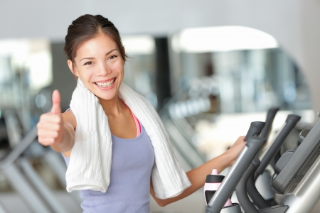 Happy fitness woman thumbs up in gym during exercise training on moonwalker treadmill. Stock Photo