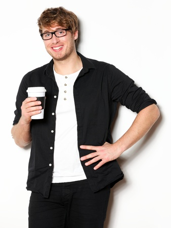 Young man drinking coffee portrait. Smiling happy male university student with drinking disposable coffee. Young male model in his twenties. Stock Photo