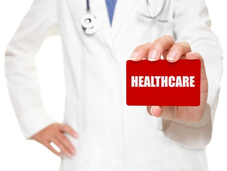 necessity: Female doctor holding a red businesscard with white capital lettering HEALTHCARE in her hand, cropped view image with selective focus to the card