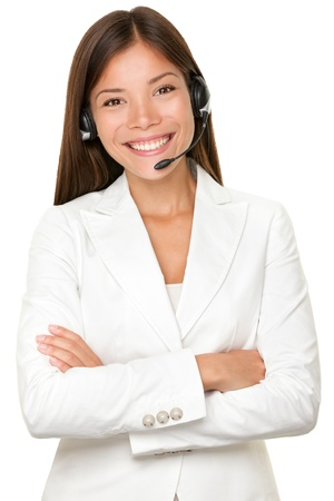 telephonist: Beautiful cheerful young Asian call operator, receptionist or personal assistant wearing a headset and microphone standing with her arms folded isolated on white Stock Photo