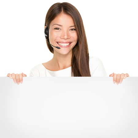 Beautiful Asian woman with a lovely smile wearing a headset and microphone holding a blank white sign in her hands for your advertising or text isolated on white