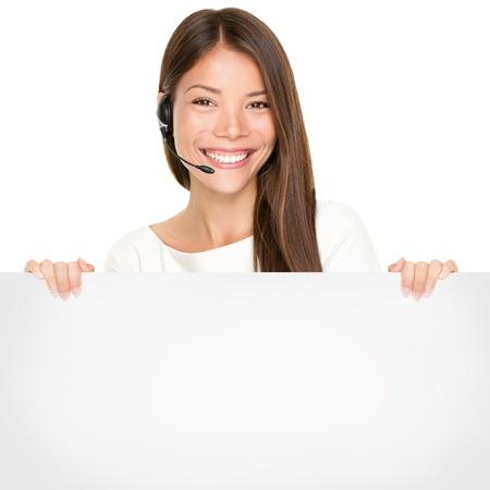 Hermosa mujer asiática con una sonrisa encantadora que llevaba un auricular y un micrófono con un cartel en blanco en blanco en sus manos para su publicidad o texto aislado en blanco Foto de archivo