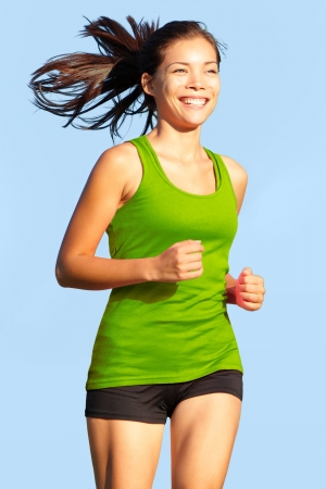 Running woman. Happy, young and athletic female fitness model in sports wear jogging outside. photo