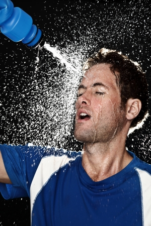 Sport fitness man. Studio shot of a young athletic man cooling himself after training by squirting water over himself from a drinks bottle photo