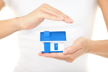 �quit�: Femme tenant une assurance habitation maison mod�le dans une main tout en formant un rev�tement protecteur avec les autres conceptuel de l'assurance habitation et de la protection Banque d'images
