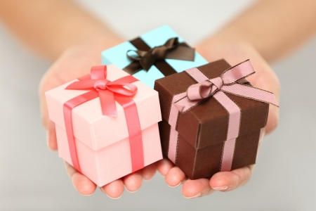 gift wrapping: Cropped view image of a woman holding three colourful Christmas gifts with decorative ribbons and bows in the palms of her her hands, can also be used for anniversary, birthday or other celebration Stock Photo