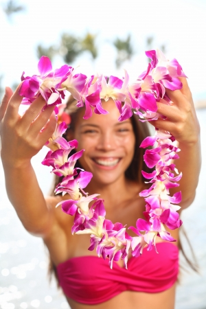 lei: Beautiful smiling mixed race woman in bikini on beach giving a welcoming Lei on the hawaiian island Big Island
