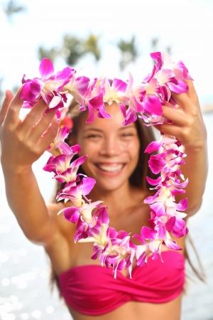 leis: Bella donna sorridente di razza mista in bikini sulla spiaggia dando una Lei accogliente della hawaiano dell'isola Big Island Archivio Fotografico