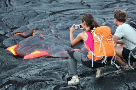 Hawaii lava tourist  Tourists taking photo of flowing lava from Kilauea volcano around Hawaii volcanoes Stock Photo