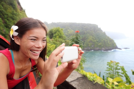 personas tomando agua: Turismo en Hawaii tomando fotos con tel�fonos con c�mara durante el viaje de coche de carretera en el camino famoso