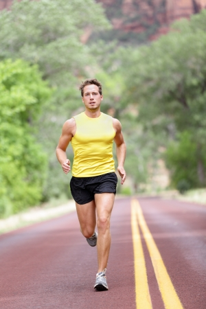 road runner: Runner man running with concentration, determination and strength in full length on road  Fit male sport fitness model sprinting outdoors