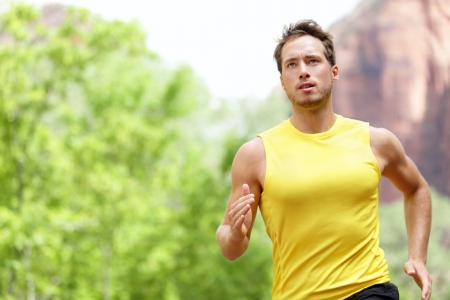 running man: Sport - Runner  Man running with concentration, determination and strength towards goals and success in marathon  Fit male sport fitness model sprinting outdoors  Stock Photo