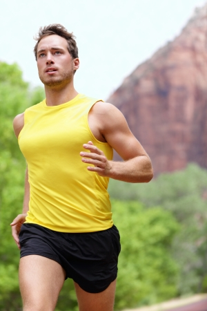 Running fitness man sprinting outdoors in beautiful landscape  Fit male runner training for marathon  photo