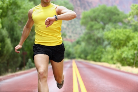 Runner with heart rate monitor sports watch Man running looking at his pulse outside in nature on road
