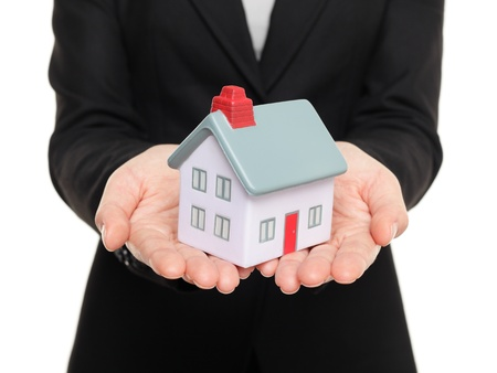 Realtor: Real estate agent showing mini house   home closeup of female realtor hands showing miniature model house isolated on white background  Stock Photo