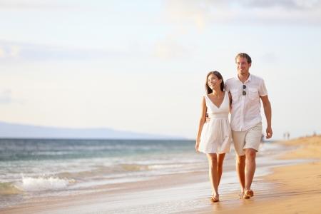 luna de miel: Pareja caminando en la playa. Joven pareja interracial feliz caminando en la explotación playa sonriente alrededor de la otra. Mujer asiática, hombre caucásico.
