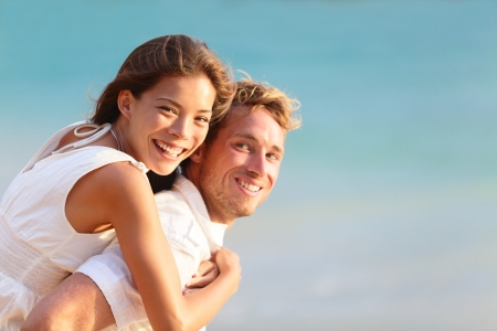 Multiracial people: Happy couple piggybacking cheerful on beach during summer holidays vacation. photo