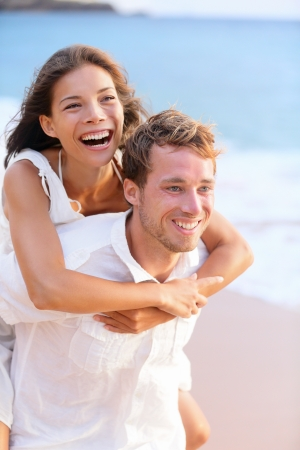 Happy couple piggybacking on beach having playful fun together during summer beach holidays. Cheerful young multiracial couple, Asian woman and Caucasian man in their twenties. Stock Photo - 17133524