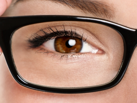 Glasses eyewear closeup. Macro of woman black eye wear glasses frame. Brown eyes of multiethnic Chinese Asian  Caucasian woman model. photo