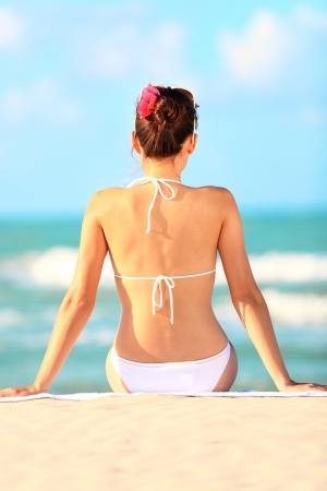 sitting down: Beach vacation woman sitting down in sand enjoying summer holidays travel. Beautiful young woman model in white bikini. From Varadero, Cuba