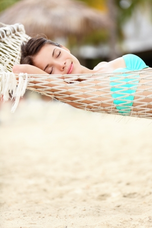Beach lifestyle woman relaxing in hammock on tropical holidays vacation. Multiethnic Asian Chinese / Caucasian model in bikini on Varadero Beach, Cuba, Caribbean photo