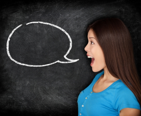 human voice: Speech bubble woman student blackboard. Woman talking in profile with black chalkboard texture as background. Funny image of mixed race female college student.