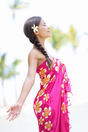 Beach woman on Hawaii relaxing enjoying the sun in serene relaxed pose. Hawaiian scene with beautiful mixed race Asian and Caucasian female model wearing sarong. Stock Photo - 17153728