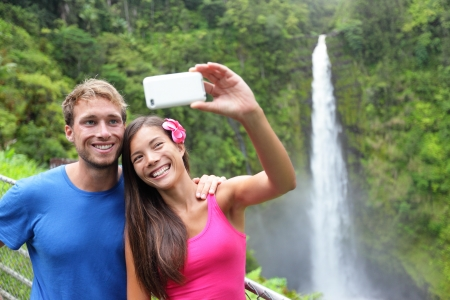 man waterfalls: Couple tourists taking self portrait with camera phone on Hawaii, Big Islands, Akaka Falls. Happy cheerful young multicultural couple on travel.