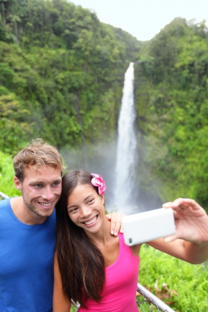 Tourists couple taking self portrait photo on Hawaii with camera phone on Hawaii, Big Islands, Akaka Falls. Happy cheerful young multiethnic couple on travel. photo