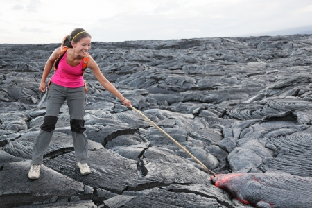 kilauea: Hawaii Big Island lava tourist on volcano poking stick in red hot moving lava. flowing lava from Kilauea volcano around Hawaii volcanoes national park, USA. Young asian woman hiker. Stock Photo