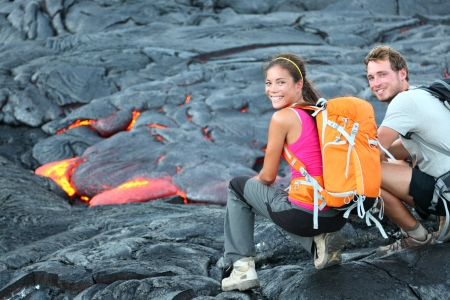 Tourists hiking near flowing lava from Kilauea volcano around Hawaii volcanoes national park, USA.