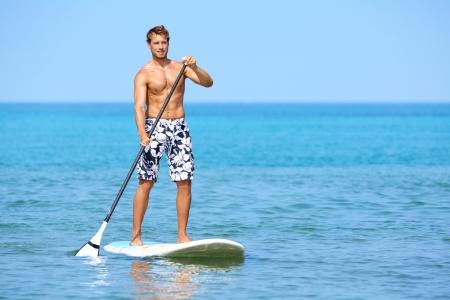 board: Young caucasian male model on Hawaiian beach on summer holidays vacation travel  Stock Photo
