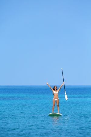 Aspirational beach lifestyle woman on paddleboard enjoying summer holidays vacation in bikini on hawaii