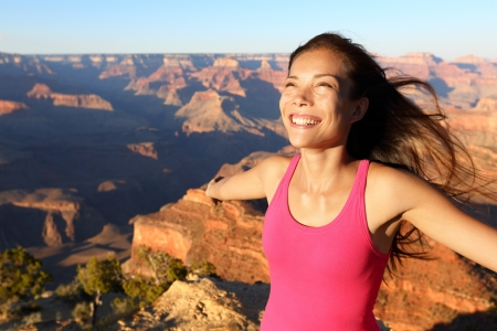 Happy freedom woman tourist in Grand Canyon smiling free in happiness during summer travel trip in Grand Canyon, South Rim, Arizona, USA  photo